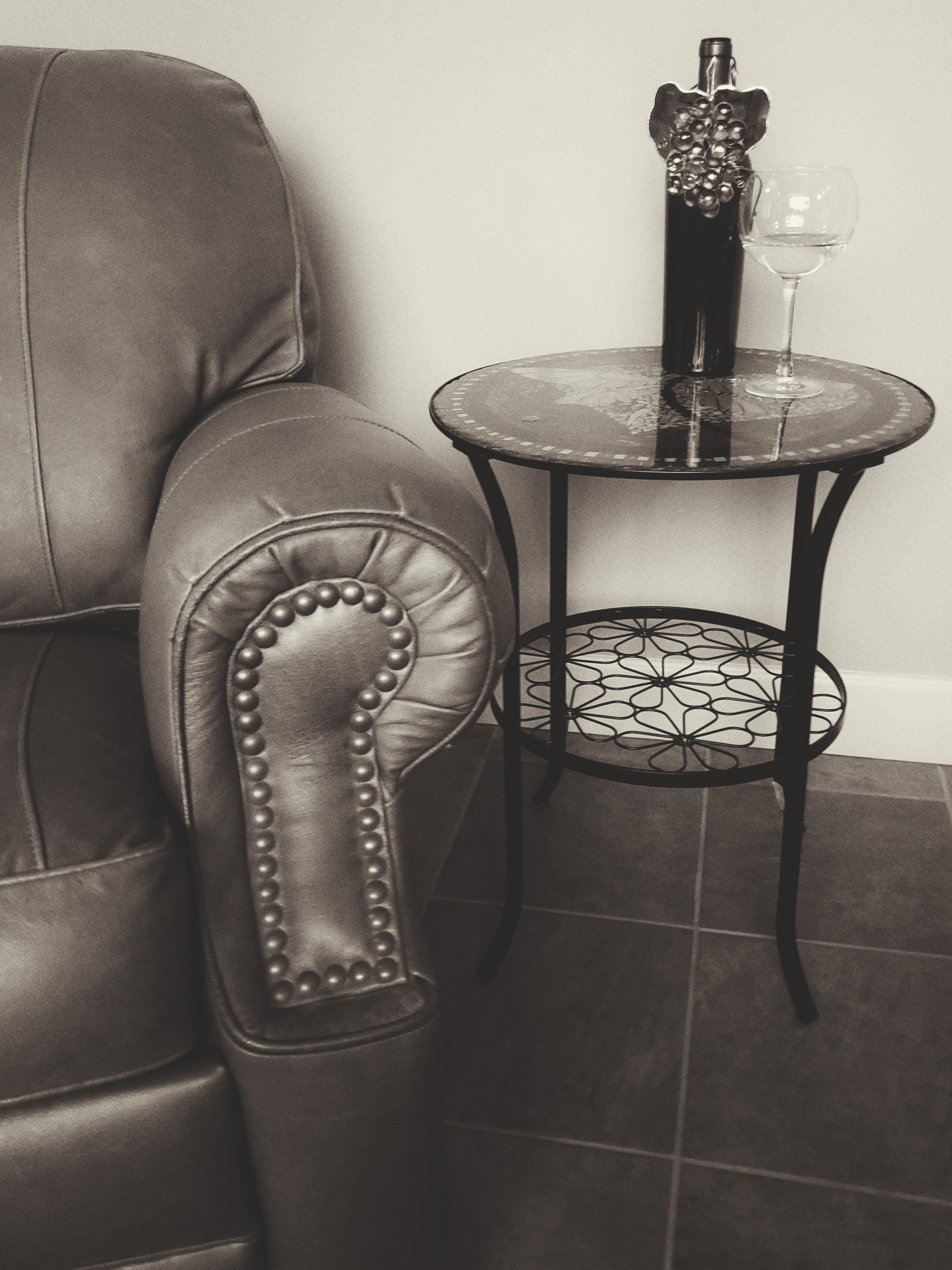 A wine bottle with a wine charm on it sits next to a glass of wine, on a glass side table, next to a leather chair.
