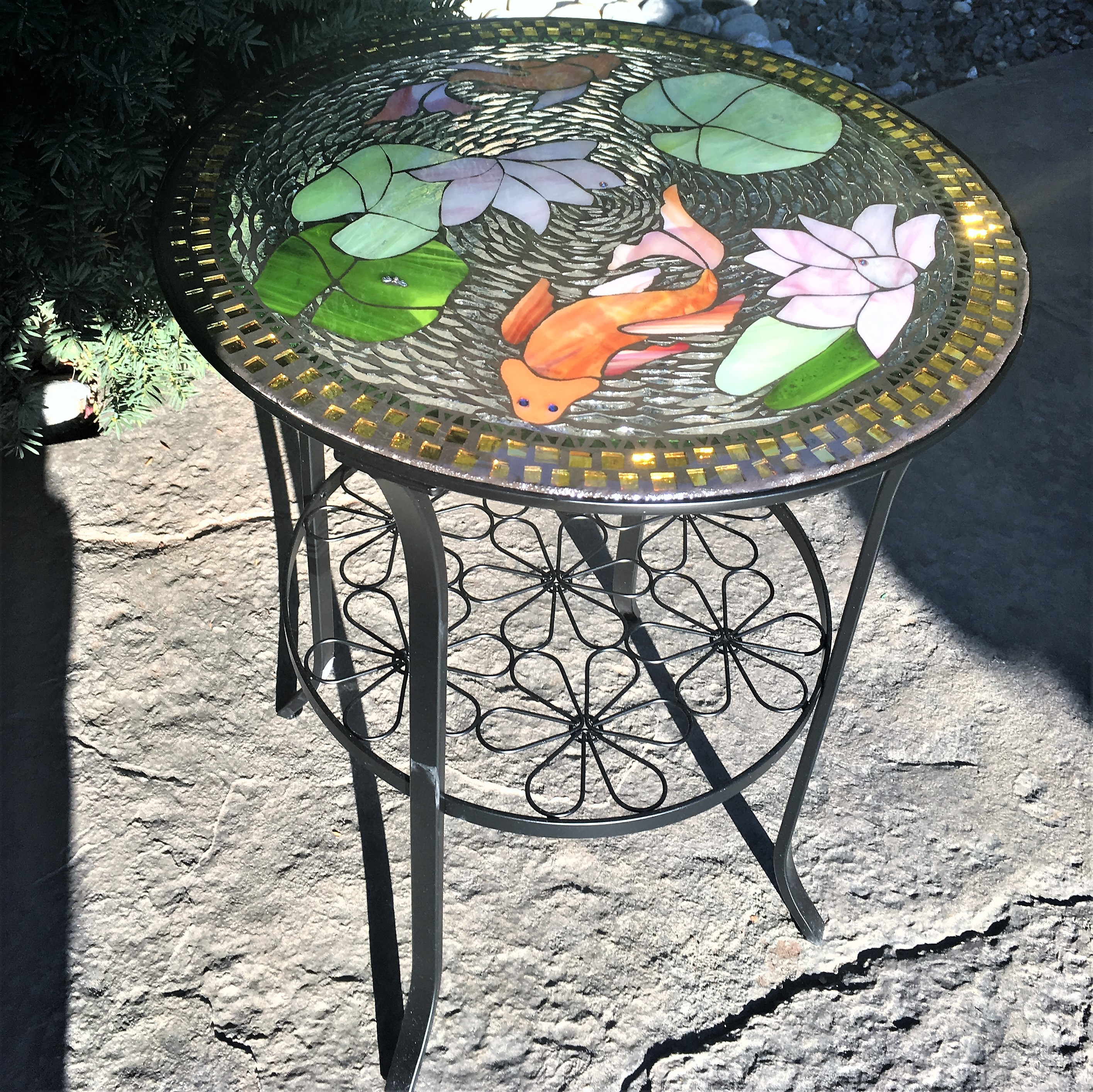 Swimming Koi mosaic glass table is seen outside on a stone floor patio.