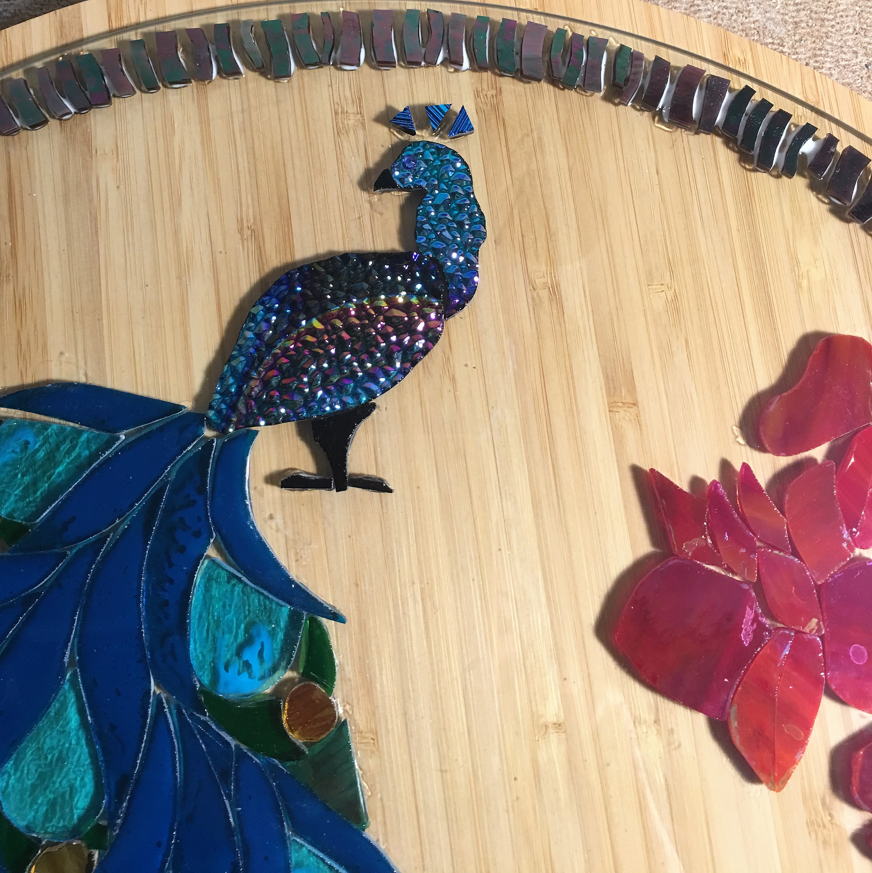 A glass blue peacock sits on a table with a glass border forming around it, as a mosiac table is created.